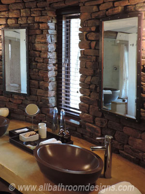 polished basin and vanity against rough brick wall